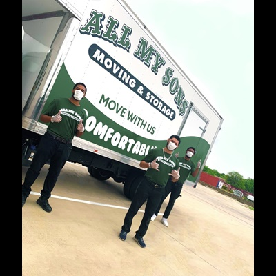 three men wearing masks in front of moving truck giving thumbs up