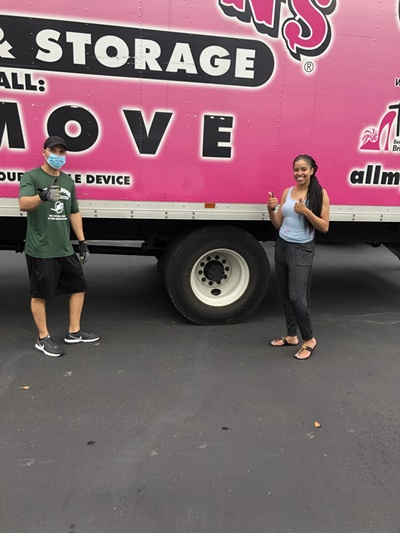Mover and client in front of pink All My Sons Moving & Storage truck in masks with thumbs up.